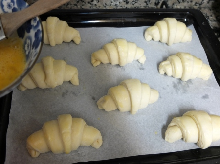 Brushing croissants with beaten egg