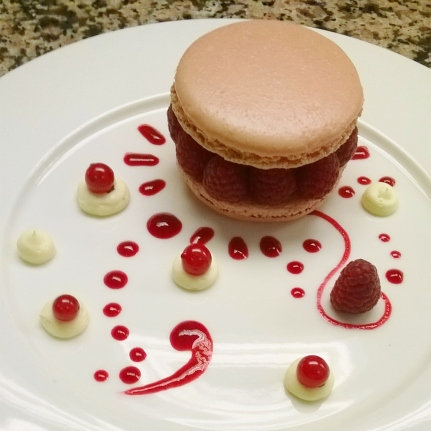 Plating a rapsberry and anis macaron with raspberry coulis and anis cream